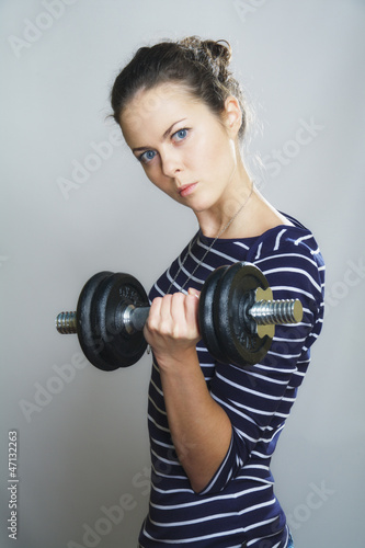serious girl with dumbbell