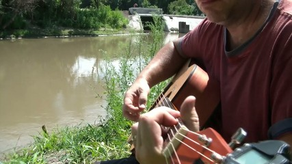 Man Playing Guitar by River