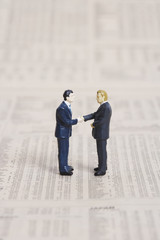 Figurines of businessmen shaking hands on financial paper