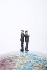 Businessmen figurines standing back to back on a globe