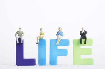 Figurines of men and women sitting on letters 'life'