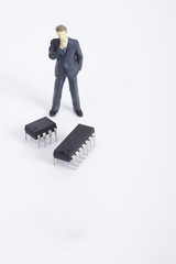 Figurines of men standing and looking at microchips