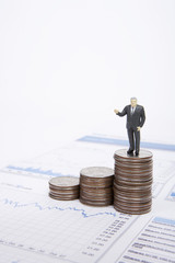 Businessman figurine standing on stack of coins