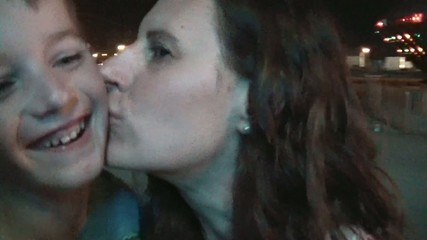 Mother Kisses Son at Fair