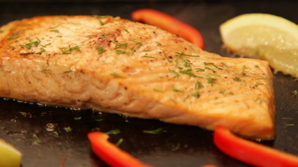 Juicy salmon fillet cooking on hot barbecue. Panning shot LR.