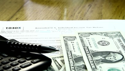 Individual US tax return document and paper money.