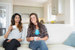Two women drinking coffee on couch