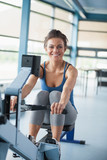Smiling brunette training on row machine