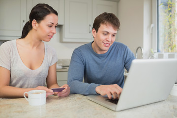 Man showing woman something on laptop