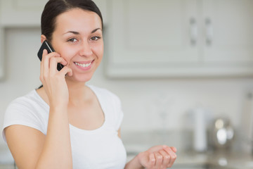 Woman calling with the mobile phone in the kitchen