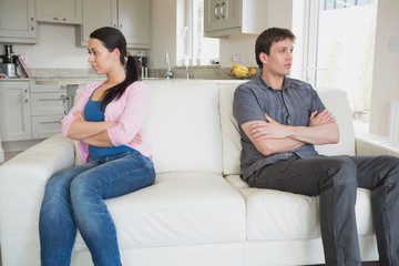 Two people sitting on the couch and having a dispute
