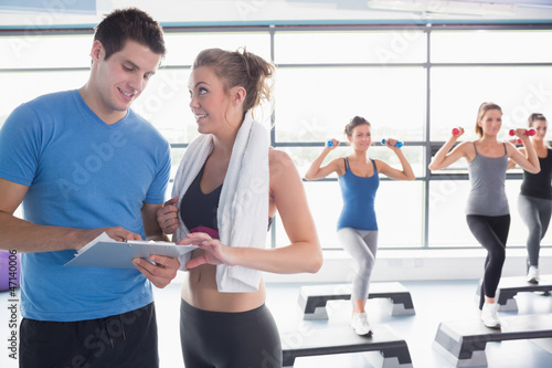 Trainer presenting timetable while aerobics class lifting weight
