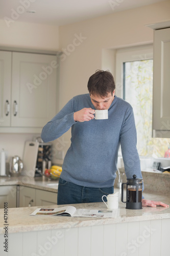 Young man having a coffee in the kitchen
