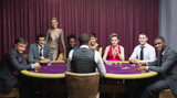 Smiling group sitting around poker table