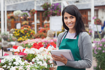 Employee making notes on the flowers in garden center