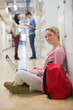 Woman sitting on the floor holding a laptop in college hallway