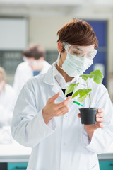 Woman standing at the laboratory holding a plant adding green ch