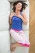Woman in pyjamas asleep on sofa