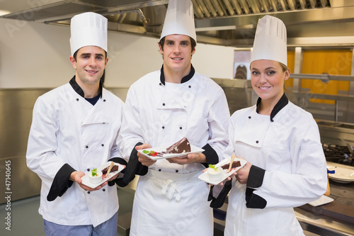 Three Chef's presenting cakes