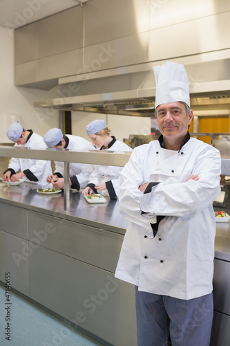 Head chef smiling with his team working behind him