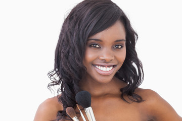 Woman smiling while holding brushes
