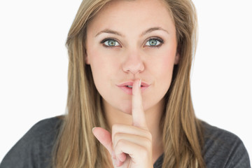 Blond woman putting finger on mouth