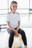 Smiling woman sitting on exercise ball