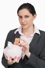 Brunette putting money into a piggy-bank