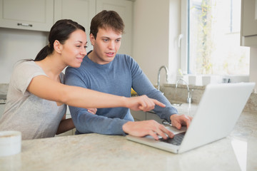 Young couple seeing something interesting on laptop