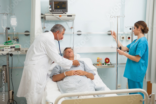 Doctor checking heartbeat of patient with stethoscope