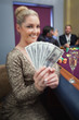 Blonde fanning dollars at roulette table
