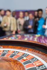 People standing looking at the roulette wheel