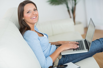 Woman sitting on sofa with her laptop