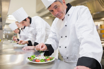 Smiling Chef's preparing their salads