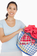 Smiling woman holding a basket full of laundry