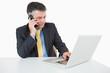 Man phoning while writing on laptop