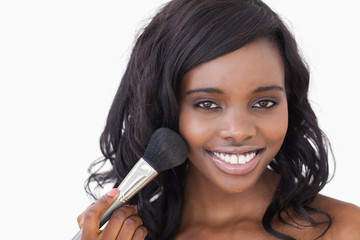 Smiling woman using makeup brush