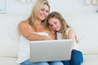 Mother showing something to her daughter on laptop