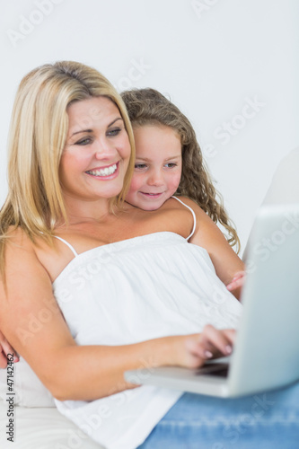 Mother using laptop with her daughter leaning on her shoulder