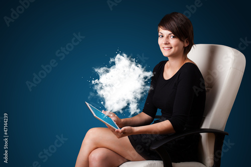 Young woman looking at modern tablet with abstract cloud