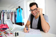 Smiling fashion designer in workshop