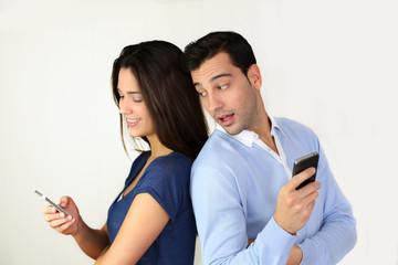 Couple standing back to back and using smartphone