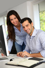 Young office workers in front of desktop computer