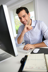 Portrait of young office worker sitting at desk