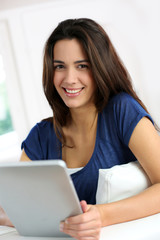 Smiling brunette girl using electronic tablet