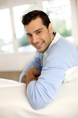 Young man with blue shirt relaxing in sofa