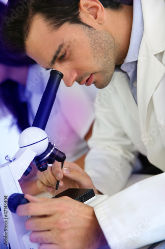 Doctor in biology working on microscope