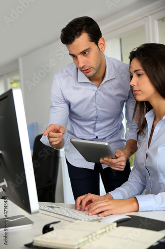 Office workers in front of desktop computer with tablet