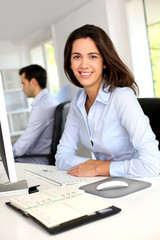 Smiling office worker in front of desktop computer