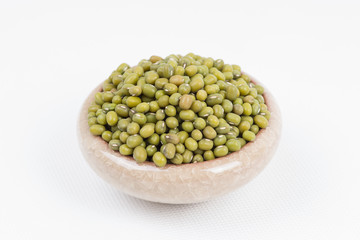 Green mung beans in bowl on white background